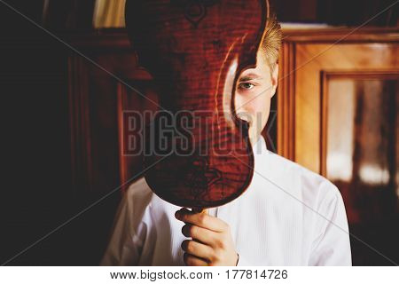Man Looks Mysterious Hiding His Face Behind A Violin