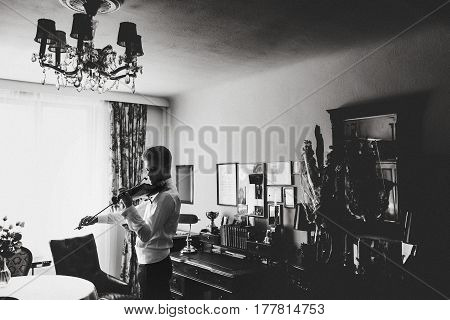 Man Plays A Violin Standing In The Front Of A Window