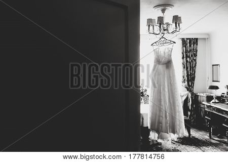 A Look From Behind A Door On A White Dress Hanging On The Chandelier