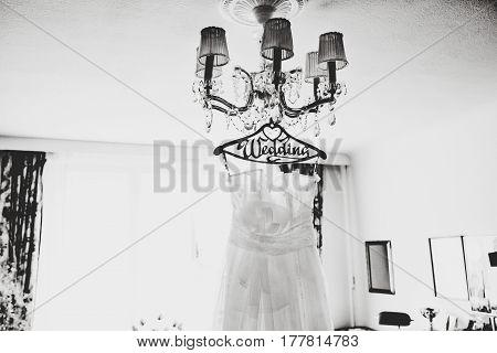 White Wedding Dress Hangs On A Chandelier