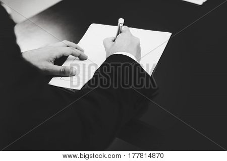 A Black And White Picture Of A Man Signing Papers
