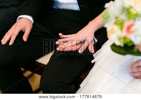 Tender Bride's Hand With A Wedding Ring Lies On The Groom's Knee