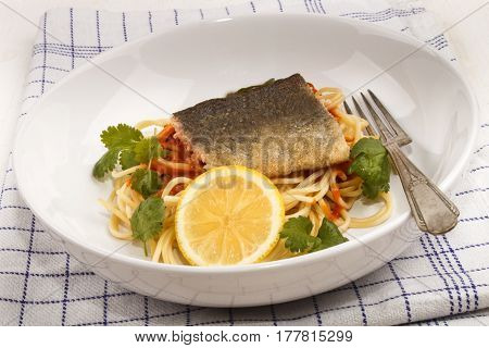 grilled trout fillet on spaghetti with tomato sauce and slice lemon