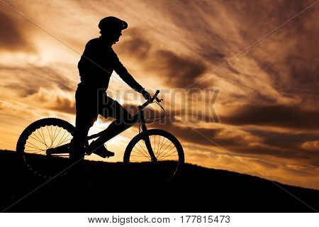 An unrecognizable man on trial bike standing in sunset lights. Horizontal outdoors shot