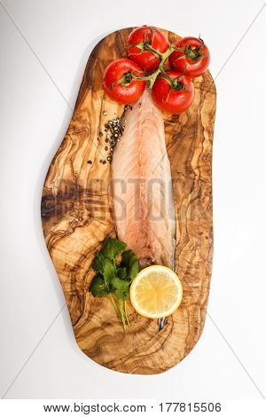 raw mackerel fillet with wet tomato slice lemon crushed peppercorn and fresh coriander on a wooden board
