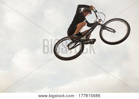 A sportsman on the bike flying over the camera on the background of the sky.