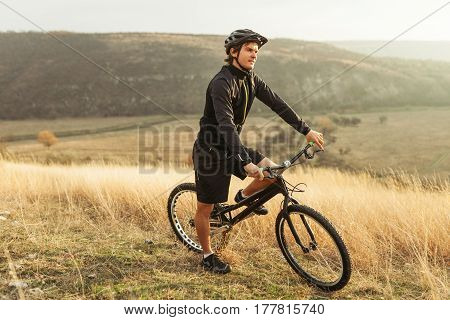 Young man on the bicycle in the mountains. Horizontal outdoors shot.