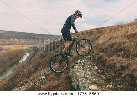 Young man climbing up to the hill with the mountain bike. Horizontal outdoors shot.