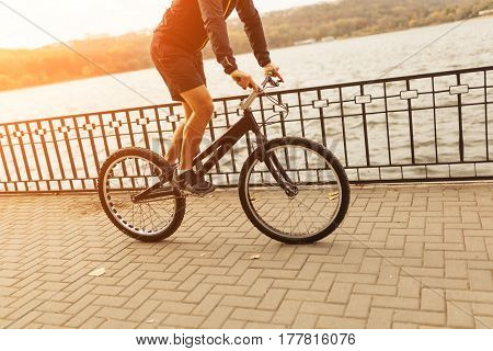 An unrecognizable person riding a trial bike on the esplanade in the city. Horizontal outdoors shot.