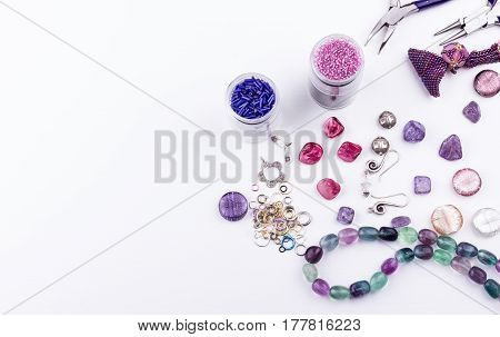 Jewelry making and beading process. Glass seed and bugle beads amethyst and turmaline stones silver toggle metal beads shell rose beads earings metal rings and pliers on white background. Hobby handmadefine arts. Top view.