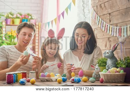 Mother, father and daughter are painting eggs. Happy family are preparing for Easter. Cute little child girl wearing bunny ears.