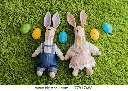 Toy Easter hare and eggs lie on the green grass