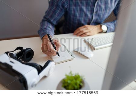 An unrecognizable man writing in the notepad with the VR goggles nearby.