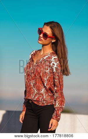 Young stylish woman in red sunglasses standing on the street