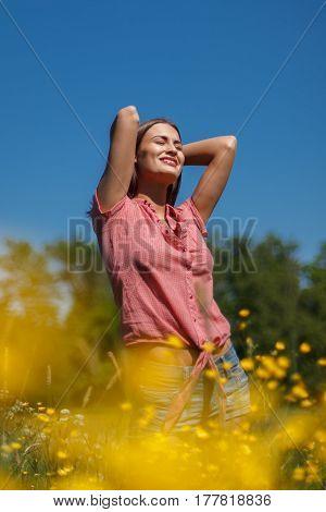 Woman enjoying summer on bright yellow field