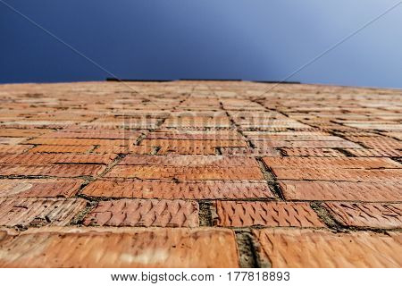 Fragment of a brick wall against the sky. Brick wall.