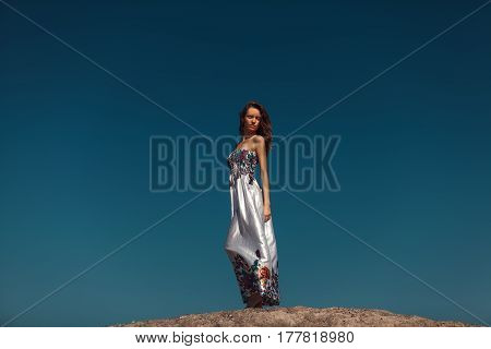 Beautiful woman with closed eyes posing over the blue sky