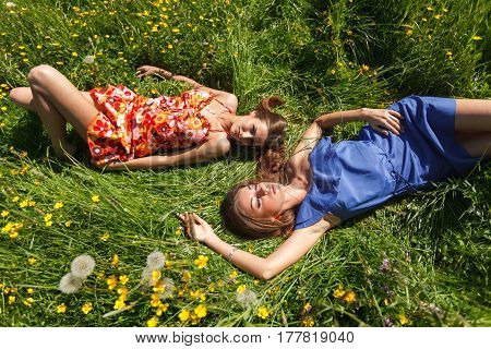 Two beautiful girls resting in the grass on a summer day