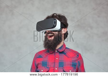 Happy man standing on the gray background and wearing virtual reality headset.