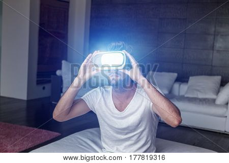 Young man with headset playing virtual reality with blue glowing artificial light