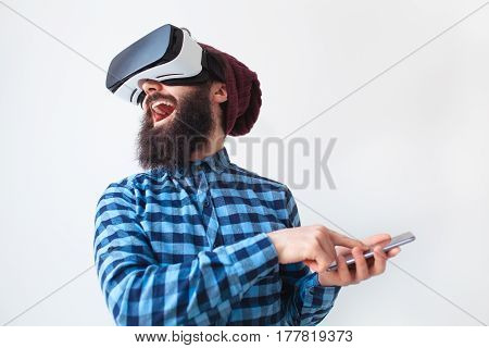 Happy bearded man using the smartphone as the VR helmet controller.