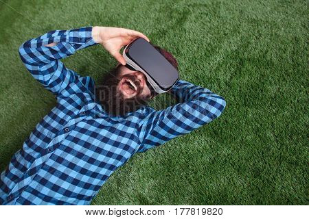 Happy bearded man with the virtual reality headset lying on a grass from above.
