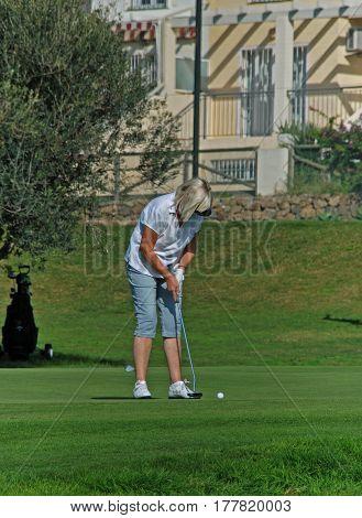 CALETA DE VELEZ, SPAIN - OCTOBER 27, 2008 - Woman playing golf at Los Llanos de Baviera Golf Caleta de Velez Malaga Province Andalusia Spain Western Europe, October 27, 2008.