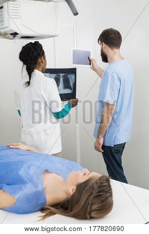 Radiologists Holding X-ray And Digital Tablet With Patient In Fo