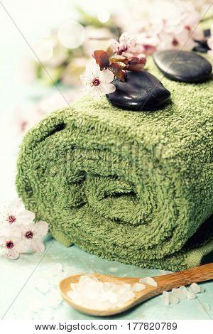 Spa setting. Massage stones, Sea salt, candles, spring flowers, towels on rustik background