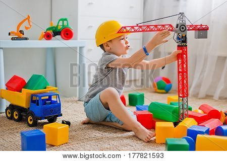 A child in a helmet on the floor plays a builder with a crane