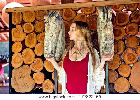 Beautiful and sexy girl model in a red bathing suit standing at a wooden wall and looking at the wooden statues of horses.