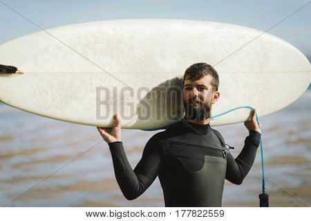 Surfer With His Surfboard Against The Sea