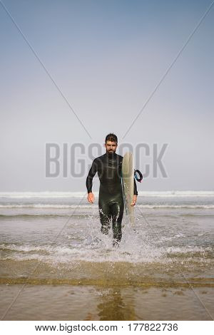 Man In Wetsuit Leaving The Water After Surfing