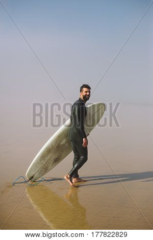 Surfer With Surfboard At Misty Beach