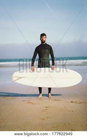 Surfer Holding His Surfboard Against The Sea