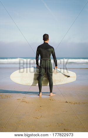 Surfer Holding His Surfboard Towards The Sea