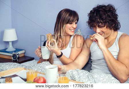 Young happy couple in love laughing and having breakfast in bed at home. Couple home lifestyle concept.