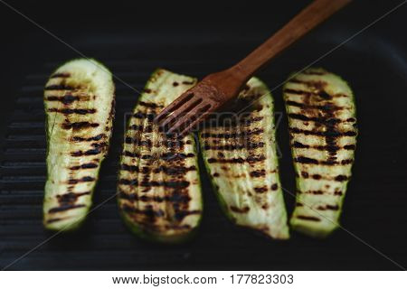 Roasted zucchini on grill pan with wooden fork.