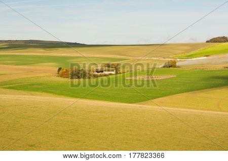 Fields and barn on the South Downs near Shoreham in West Sussex England. Coloured patterns of different field crops. With bonfire and smoke