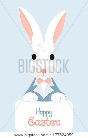 A white rabbit with pink ears in a blue jacket with a bow holds in his paws a card with the hand written inscription Happy Easter