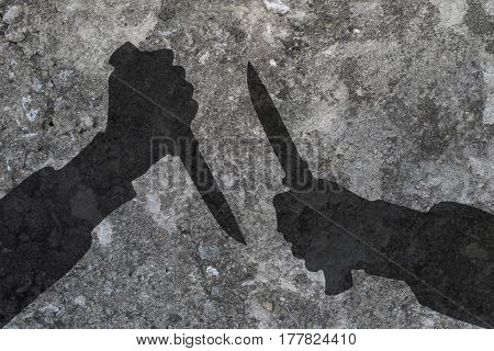 Two human hands with knives silhouette in shadow on concrete wall background with space for text or image.