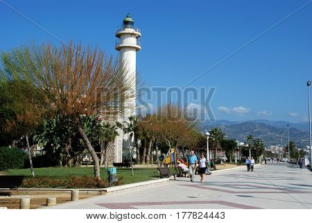TORRE DEL MAR, SPAIN - OCTOBER 27, 2008 - Tourists walking along the promenade with the lighthouse to the left hand side Torre del Mar Malaga Province Andalusia Spain Western Europe, October 27, 2008.