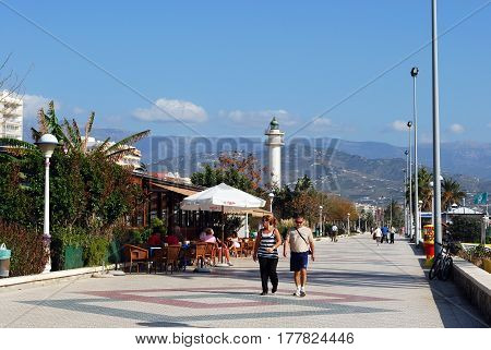 TORRE DEL MAR, SPAIN - OCTOBER 27, 2008 - Tourists and pavement cafes along the promenade with the lighthouse to the rear, Torre del Mar, Spain, October 27, 2008.