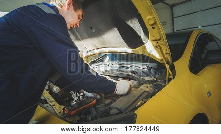 Mechanic in car repairing service - diagnostics in engine compartment, close up