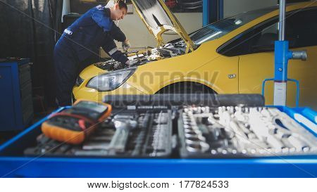 Car auto electronics - mechanic repairs a car - unscrews detail of automobile - garage service, horizontal