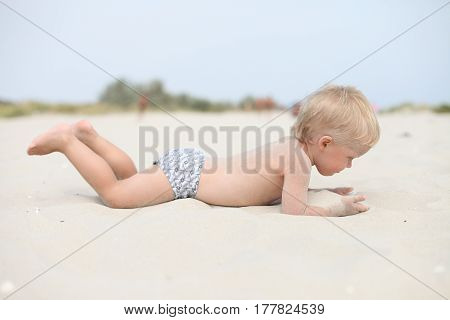 Little boy is playing in the sand