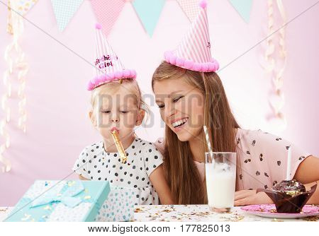 Lovely girl whistling, having fun at birthday party at home. Young family celebrating anniversary.