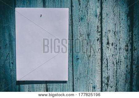 white sheet of paper hangs on a blue wooden wall empty space on the right