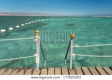 Pier in the sea in resort. Summer vacation. View at a clear sea with turquoise water. Summer vacation at a sea coastline in a exotic country. Swimming in a warm clear turquoise water.