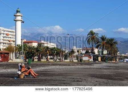 TORRE DEL MAR, SPAIN - OCTOBER 27, 2008 - Woman sunbathing on the beach reading a book with views towards the lighthouse Torre del Mar Malaga Province Andalusia Spain Western Europe, October 27, 2008.